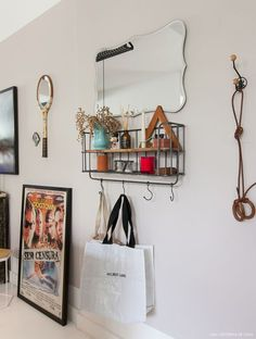Hall de entrada tem organizador de ferro, espelho e ganchos para pendurar bolsas.