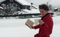 A Norwegian man casually slides down an icy road wearing a dressing gown with   a book in one hand and a coffee in the other