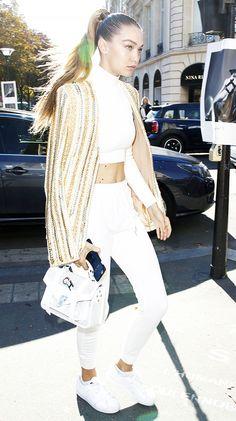Gigi Hadid wears a Balmain jacket, crop top, high-waisted white pants, a Proenza Schouler bag, and sneakers