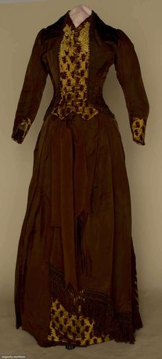 BROWN SILK BUSTLE DRESS, 1880s Chocolate brown faille & brown velvet cut to copper satin in small grape clusters, bodice w/ copper round bead trim & ecru lace, pleated a-symmetrical skirt, silk fringe trim on 1 panel.
