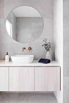 Clean lines and large format grey tile covers the floor and walls. A round frameless mirror hangs over a white sink with brass wall mounted bathroom sink faucet. The flat paneled vanity is wall mounted and has a thin white countertop Bathroom DOT + POP Wall Mounted Bathroom Sinks, Bathroom Sink Faucets, Small Bathroom, Master Bathroom, Bathroom Tiling, Grey Bathroom Tiles, Modern Bathroom Sink, Vanity Bathroom, Modern Bathroom Design