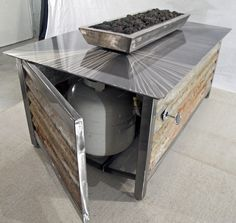 Modern industrial outdoor steel fire table with stainless steel burner and fire box and powder coated exterior panels for burning propane or natural gas. Made in the USA.