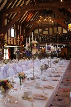 tall silver candelabra centrepieces with country garden summer flowers. Photos of wedding centrepieces in the tithe barn, with banqueting table layout. Summer wedding at Great Fosters