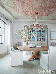 Or so goes the thinking behind this new California beach house planted in the sands of Orange County. Its owners, Laureen and David Demshur, live in Houston, and they wanted a magical place to unwind in style with friends on long weekends.  An 18th-century Italian painted ceiling infuses the dining room with subtle color and patina. Custom table. Custom chairs in Browning & Chandler fabric and Samuel & Sons trim. Chandelier, Niermann Weeks. Italian 18th-century cabinet. Rug, Caravan Rug…