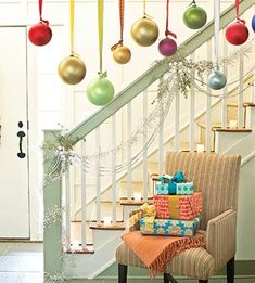 """Hang oversize ornaments in the foyer or near staircase.  From Ladies' Home Journal:  """"we secured oversize glass balls hung from wide ribbons to the bottom of the second floor handrail. This whimsical idea can also work to dress up a window or an interior door frame -- just be sure to hang them high enough so guests won't bump them when passing through."""""""