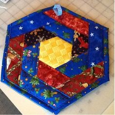 """This is a great scrapbuster! I used scraps of Christmas fabrics, and my next one will be in reds and pinks for Valentines. Quilt as you go Hexagon Hot Mat Supplies: 15"""" square of a busy print..."""