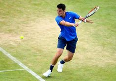 Bernard Tomic trying to return the ball with a backhand shot in a match of the Aegon Tournament against Gilles Muller on June 17, 2016...