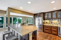 #KitchenRemodel in #DesMoines: Floor to ceiling windows, granite countertops, oak cabinets, wooden floors, and a very modern backsplash and modern kitchen design. http://www.powellrenovations.com/custom-seattle-renovations/remodeling-services/kitchens
