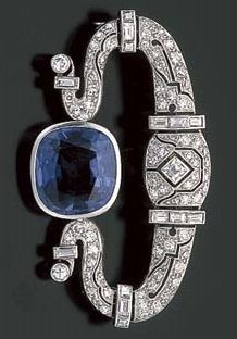 ART DECO SAPPHIRE AND DIAMOND BROOCH. Set throughout with small round diamonds, centring a cushion cut bezel set sapphire, mounted in platinum, circa 1930.