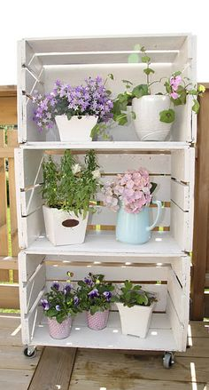 Shelving for Patio. Wood Crates (sell at Hobby Lobby) Paint and add wheels to them and a few color Flower Pots!