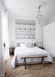 These high ceilings, all white palette and rustic wood bench are all on our list of style picks! These unfinished herringbone wood floors might take the cake in this bedroom.