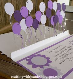 handmade birthday card tutorial from Crafting with Joanie: How to Make a Pop Up Balloon Card ... acetate panel pops up ... lots of Cricut cut balloons in purples ...