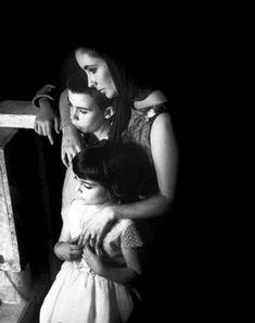 Elizabeth Taylor fotografada junto aos filhos Michael Wilding Jr. e Liza Todd no set do filme Becket, em 1963. Os três assistiam Richard Burton atuando em uma cena de morte. Photo de Eve Arnold.