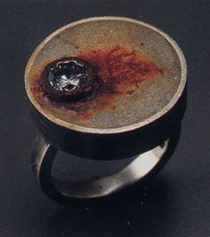 concrete ring with rust and embedded diamond.