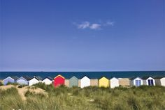 Wodden Fence at beach with huts in the Background