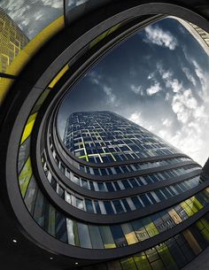Urban Architecture Photography by Nick Frank. Low angle of buisness building, emphasizing the swooping curve of the lower ongoing rooms near photographer against the height of the main building. Clouds look almost swirling around it - Fish eye lens?