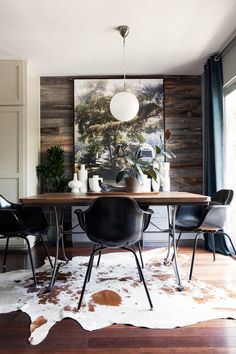 Plants and a big photograph of a forest are the perfect addition for this room with all its wood on the floor, table and wall. It's almost like being outside, but a very cosy and warm outside.