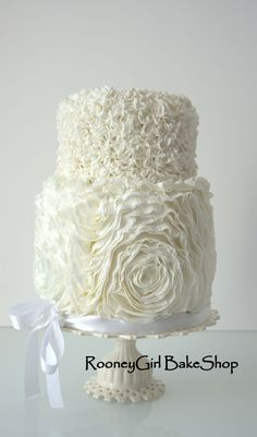 This is a small wedding cake. I used Sharon Wee's tutorial to make the ruffle roses on the bottom tier.  The top is made up of scrunched up little fondant circles. This is one of the prettiest cakes I've ever made. I wish I had more opportunities to do these.  Enjoy!