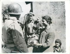 1944- U.S. 5th Army soldier distributes the anti-malaria drug Mepacrine to Italian Families in Anzio, Italy.