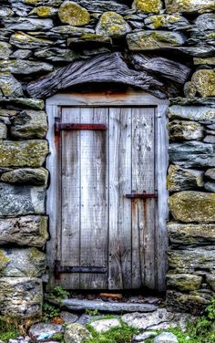 Lake District, Cumbria, England weathered grey door -- the wood above the door, along with the off-kilter-yet-not cut of the entire thing lends a combination of primitive quality and clever, artful know-how.