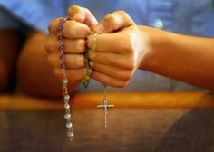 A child holds rosary beads