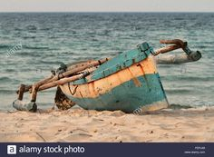 An indigenous fishing boat or canoe or type of dhow is lying on the beach sand of Pemba mozambique. Stock Photo