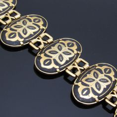 Wide damascene bracelet has wide oval links in gold tone metal with striking damascene almost panel style. Push in clasp, 7 inches long and 1 1/6 inch wide. Very good vintage condition - the back needs cleaning and the safety chain is missing.  Find lots more vintage jewelry at Purple Daisy Jewelry! http://www.etsy.com/shop/purpledaisyjewelry  Thanks a bunch for shopping for vintage jewelry at Purple Daisy Jewelry on Etsy