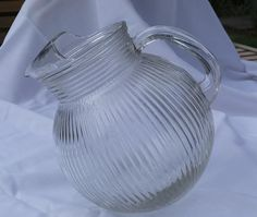 This is a nice vintage glass pitcher with a ribbed tilt ball design. The ice catcher lip makes pouring so much easier. The pitcher measures 8 tall by