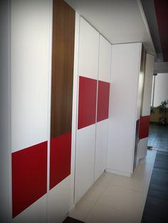 Panel decorativo en hall de recepción. Es closet para guardado de carpetas y elementos de oficina. Puertas enchapadas en duotono y con repisas interiores móviles.