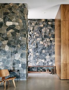 In the entryway of this modern house, grey stone lines the walls while American black walnut has been used for the wood cabinets. A wooden shoe rack helps keep the family shoe collection under control and an exposed hanging bulb brightens the hall and adds a rustic touch.