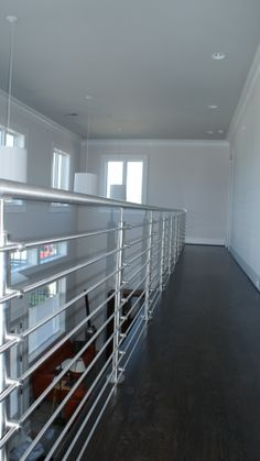 """A bit of a departure from form for the Vertheen residence. Here, we installed new 1-2/3"""" 304 stainless steel railings and newel posts. The stainless posts are accompanied by our horizontal round bar and our 1-2/3"""" wall stainless steel wall rail. The over all effect – sleek and stylish."""
