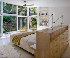Valorizada pela decoração neutra, a vista é o destaque deste ambiente, que conta com uma cama flutuante apoiada no armário e virada para a parede de vidro.