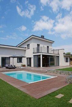 Těžištěm domu je společná obývací část s prosklenou rohovou stěnou, orientovaná na terasu a k bazénu.
