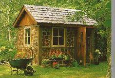 Garden shed built of cedar log rounds set in cement.