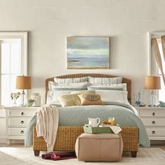 Introduce a coastal theme to your bedroom with a wooden framed bed and array of blue and white pillows and bedding. Accompany these with a watercolour painting of the coast to give you that holiday feeling.