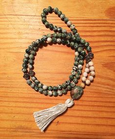 This mala necklace is made with the traditional 108 beads. This necklace is made with moss agate, grey agate and garnets with a howlite guru bead.