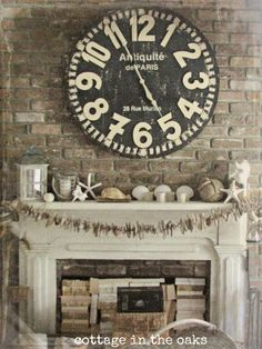 Vintage summer mantel, love driftwood garland and stacks of books in the fireplace!