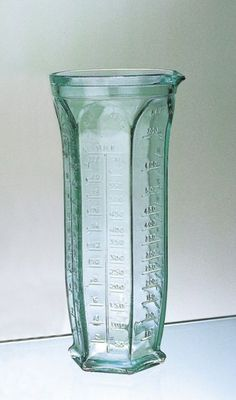 Tall, 6-sided green glass measuring jug provides units for dry and wet measurements.