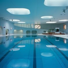 Rounded windows and skylights allow daylight to filter into this Parisian swimming pool by Mikou Studio which features a grassy rooftop solarium. The architects used Feng Shui philosophy to determine the best way to orientate elements creating an uncluttered layout with an abundance of natural light. Find out more on http://ift.tt/1EbrUAD by dezeen