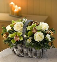 Orchid Christmas Flower Basket. Presented in a classic wicker basket, this arrangement of stunning orchids, white Avalanche roses and freesias is surrounded by noble pine and frosted eucalyptus, finished with lime slices for an extra fresh touch and a Christmassy feel. 3 x White rose Avalanche 3 x Green orchid heads 3 x Lime slices 4 x White freesia 4 x Noble pine 2 x Eucalyptus parvi frosted Presented in a classic wicker basket Wicker basker dimensions: Sent with a card for your personal…