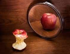 This pin of an apple and the mirror is a metaphor as to how Leah sees herself(eaten one.)and how the rest of the world and everyone else sees her.(uneaten one.)