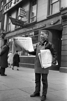Paperboy selling the Irish Times outside Aer Lingus office on O'Connell Street, Dublin. 12th February 1963.