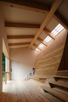 A wooden floor that curves up to become a wall allows light and air to flow through this bathhouse in Japan.