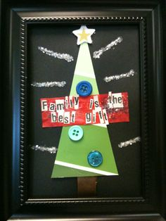 """My students created this 5x7 project for Christmas gifts. They turned out great! We used paint chips for the tree, buttons for the ornaments, sticky-backed foam stars for the topper, and brown ribbon glued underneath for the tree stump. Newspaper letters glued to the tissue strip spelled, """"Family is the Best Gift."""" 4th Grade, 2011"""