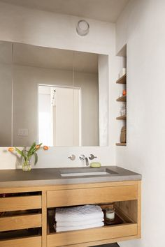 A concrete countertop sits atop a custom white oak vanity. The wall-mounted chrome faucet is from Graff.