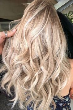 Champagne Blonde With Highlights | We love a glass of champagne to celebrate a special occasion (or just weekend brunch), but the bubbly drink is now making its way into salons—in the form of a gorgeous new hair color. Apparently, hair colors inspired by drinks are already a thing, and champagne hair is just the latest pin to tack on to 2018's hair color trends. You might picture champagne hair as simply another blonde but it's much more versatile.