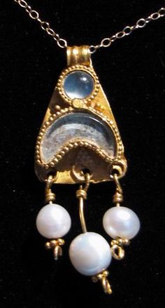 Greek Gold Pendant with Pearls  An ancient Greek gold pendant with a solar and lunar motif inlaid with aquamarine and three dangling antique natural pearls.  Ca. 4the century BC.   Height: 35 mm.