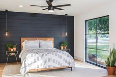 On this week's Fixer Upper the former garage was transformed into an edgy master suite with modern design details like the black accent wall, a contemporary styled ceiling fan, updated lighting and simple, modern furnishings. And look at those windows! Click the link in bio to see more of this ultra-modern house.