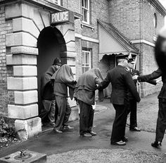 Under the guidance of police officers, three hooded men are taken to waiting police cars at Linslade, Buckinghamshire, after being remanded in custody on charges in connection with the great train robbery the previous week. Two women were also remanded in custody.