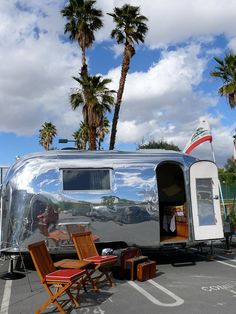 Vintage Airstream set up with heavy wooden chairs.